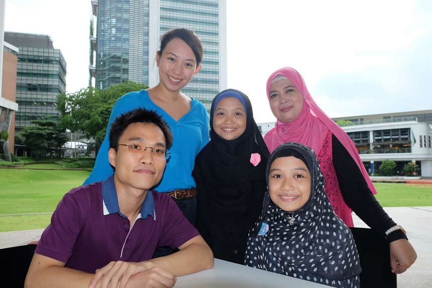 Nur Dhamirah Amiszan (right, sitting) and her sister Nur Bhatrisyia Amiszan (standing), with their mother, Hafidatun Athali (right), Lynette Wong (left, standing) and tutor Brian Teo.