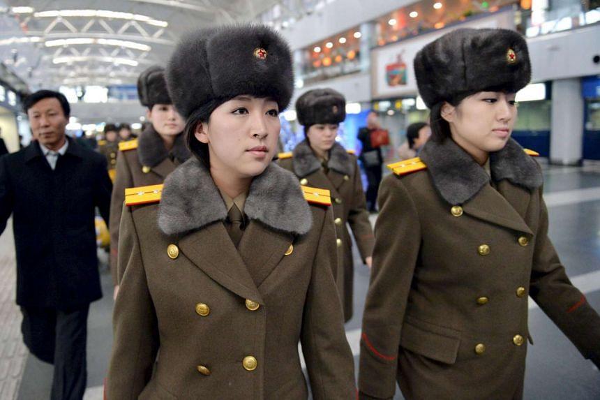 Members of the Moranbong Band of North Korea arrive at Beijing International Airport before departing from Beijing.