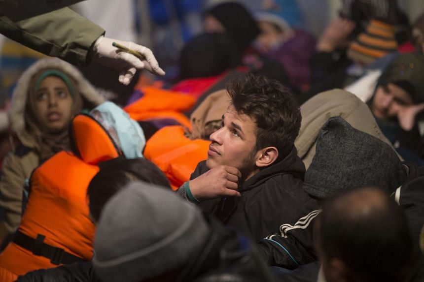 Members of Turkish Coast Guard ship UMUT register Syrian migrants after capturing a boat carrying them at the Aegean Sea.