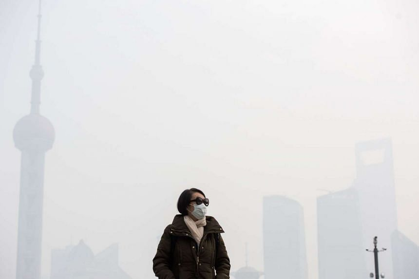 A woman wearing a face mask on a heavily polluted day in front of the financial district of Pudong, Shanghai.