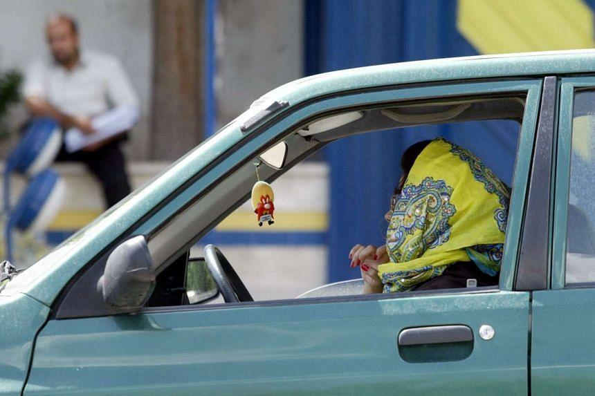 An Iranian woman driving her car in the capital Teheran.