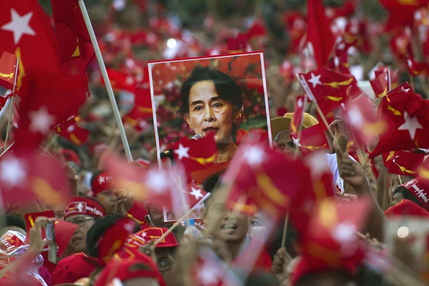 Supporters of Myanmar opposition leader Aung San Suu Kyi hold posters bearing her image as they listen to her speak during a campaign rally for the NLD in Yangon.