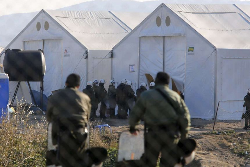 Greek police officers guard the perimeter where hundreds of migrants are gathered in tents.