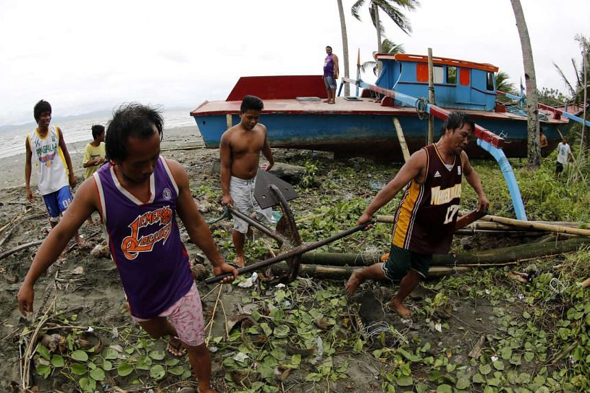 Filipino fishermen carry an anchor as they secure a fishing boat in the town of Atimonan, Quirino province, southern Manila, Philippines, on Dec 14, 2015.