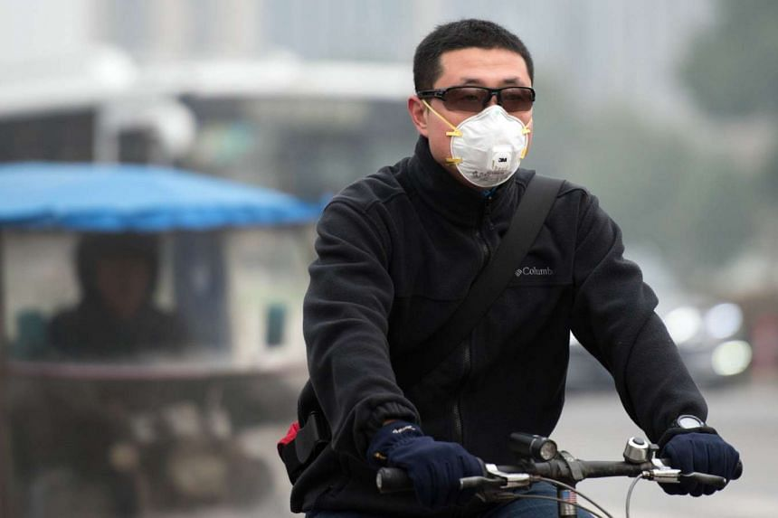 A man wears a face mask as he commutes on his bicycle on a heavily polluted day in Shanghai.