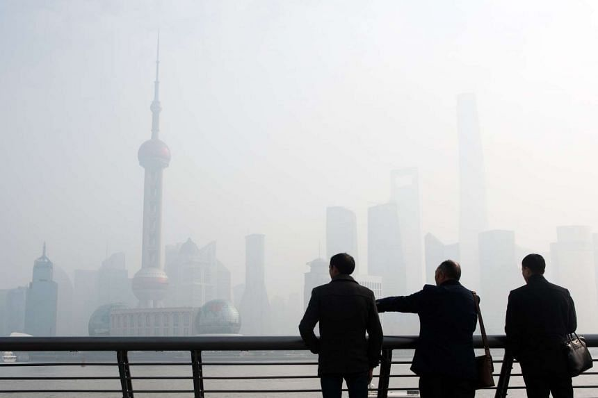Men stand along the Bund in front of the financial district of Pudong, Shanghai.