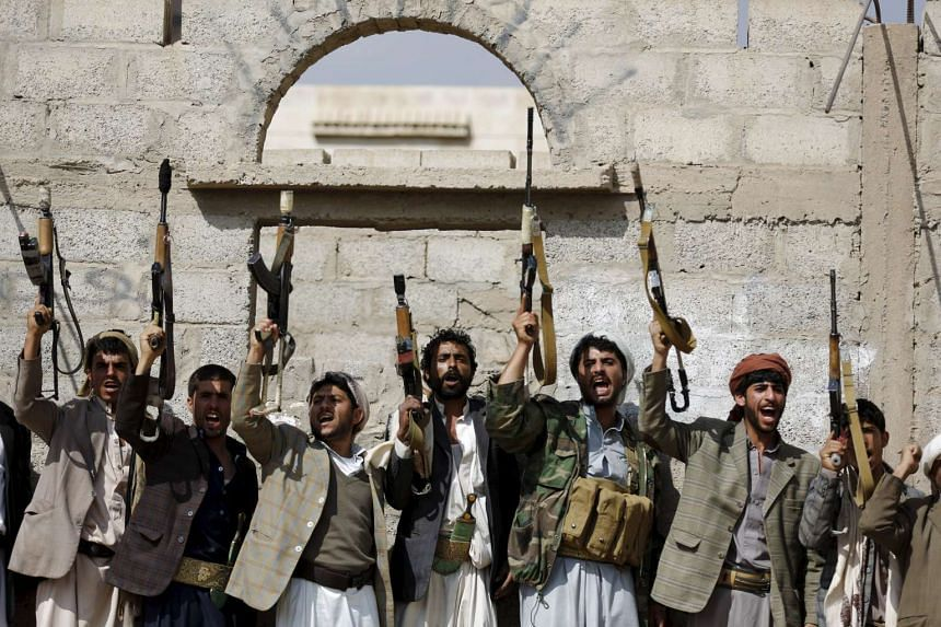 Tribesmen loyal to the Houthi movement shout slogans and raise their weapons during a gathering to show their support for the group.