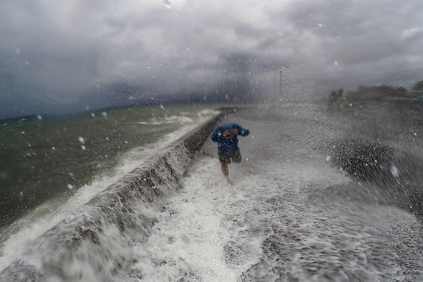 A resident walks past big waves spilling over a wall onto a coastal road in the city of Legazpi, south of Manila on Dec 14, 2015.