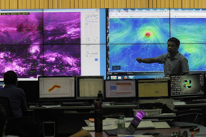 Meteorologists from the Philippine Atmospheric Geophysical and Astronomical Services Administration (PAGASA) monitor and plot the direction of powerful Typhoon Melor at their headquarters in Manila.