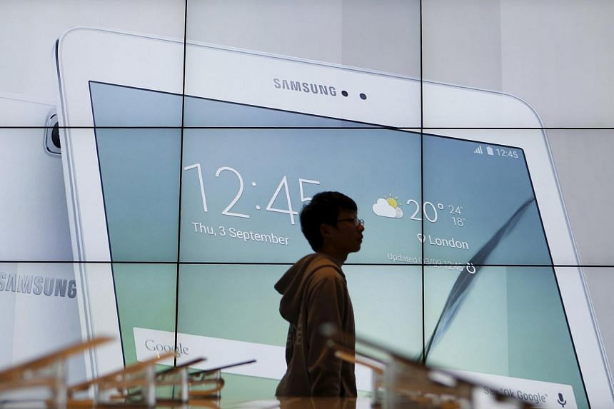 A student walks past an electronic display promoting Samsung Electronics products at the company's headquarters in Seoul.