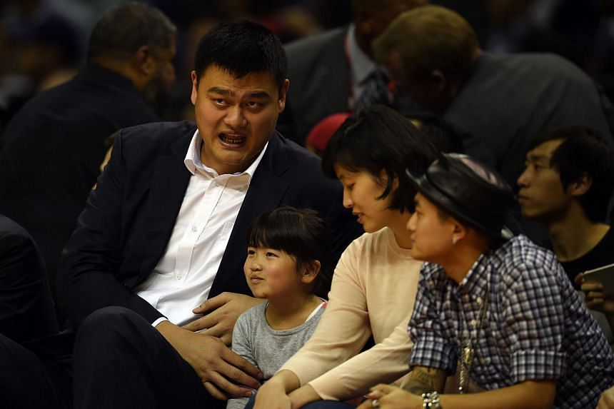 Yao Ming (left) follows the 2015 NBA Global Games China pre-season basketball match between the Charlotte Hornets and Los Angeles Clippers in Shanghai, Oct 14, 2015.
