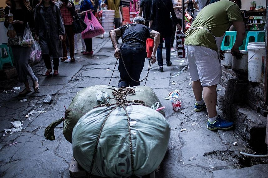 """A load being hauled uphill in Chongqing, which is known for its hilly terrain. Its many slopes led to the formation of an informal trade involving porters, known as the """"bang bang army"""", who help residents carry things using poles balanced on their s"""