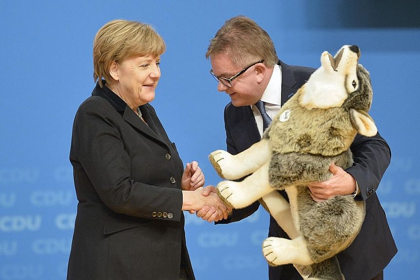 German Chancellor and leader of the Christian Democratic Union Angela Merkel receiving a toy from Mr Guido Wolf, the party's top candidate in the upcoming state elections in Baden-Wurttemberg, where the CDU staged a show of unity at a pivotal congres
