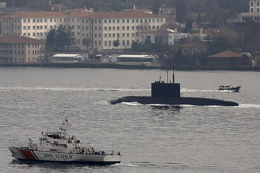 A Russian submarine being escorted by a Turkish Navy Coast Guard boat in the Bosphorus, on its way to the Black Sea, on Sunday. Yesterday, a Russian-run energy firm in Crimea said a Turkish vessel did not give way to a convoy of Russian ships, includ