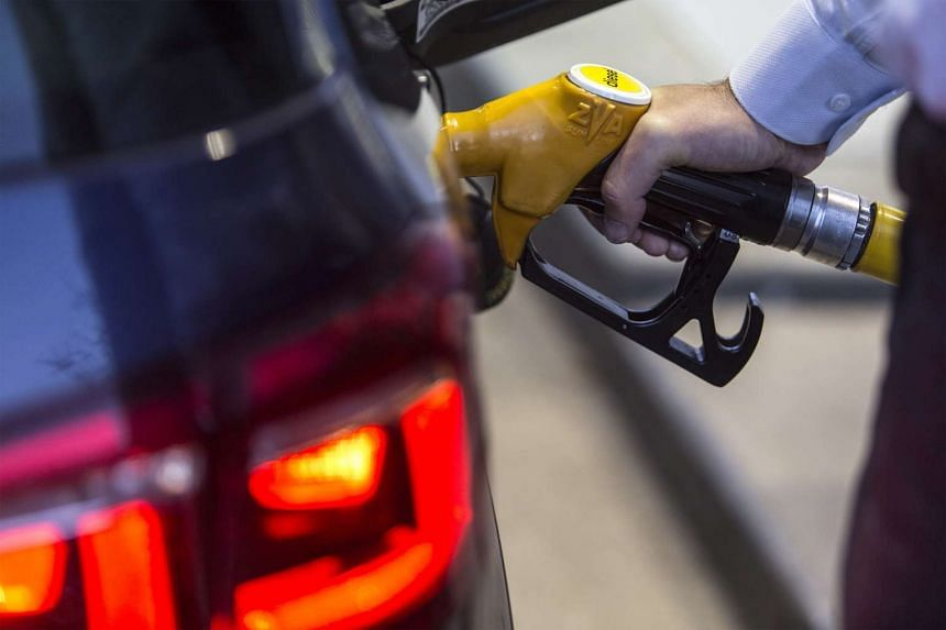 A customer refuels his car at a gas station operated by Total SA in Luc-La-Primaube near Rodez, France, on Dec 11, 2015.