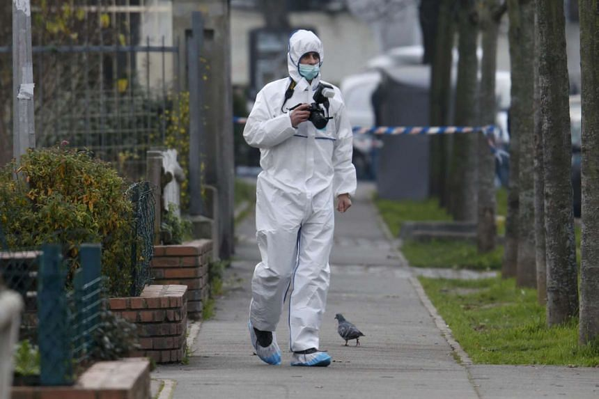 French police investigator works at the nursery school near Paris where a teacher claimed he was attacked by a hooded man acting for ISIS on Monday.