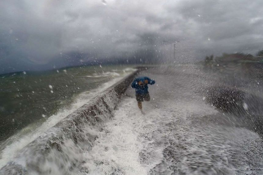 A resident walks past big waves spilling over a wall onto a coastal road in the city of Legaspi in Albay province, south of Manila on Dec 14, 2015, as typhoon Melor approaches the city.