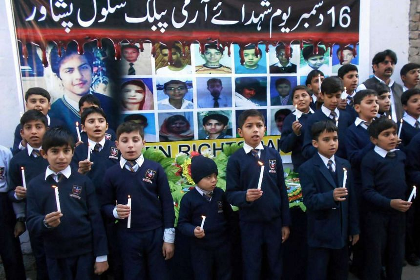 Pakistani students hold candles as they mark the first anniversary of the Peshawar school massacre.