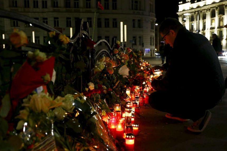A man lights a candle for the victims of the Paris attacks in front of the French embassy in Vienna, Austria.