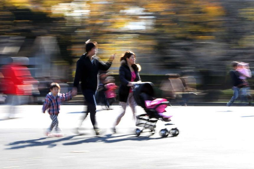 A Japanese family strolling in a park in Tokyo.