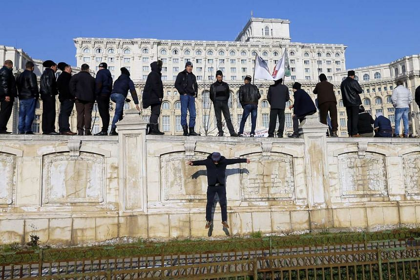 A Romanian shepherd (centre) jumps off while his colleagues wave flags and shout slogans after climbing the protective fence surrounding parliament's yard, in front of Romania's Parliament Palace (background), during a protest in Bucharest, Romania,