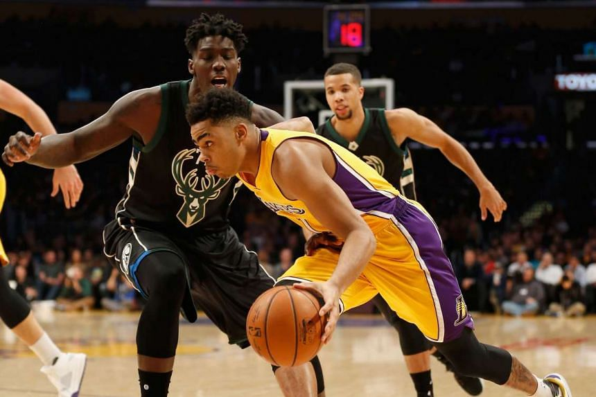 D'Angelo Russell of the Los Angeles Lakers dribbles past Johnny O'Bryant III of the Milwaukee Bucks.