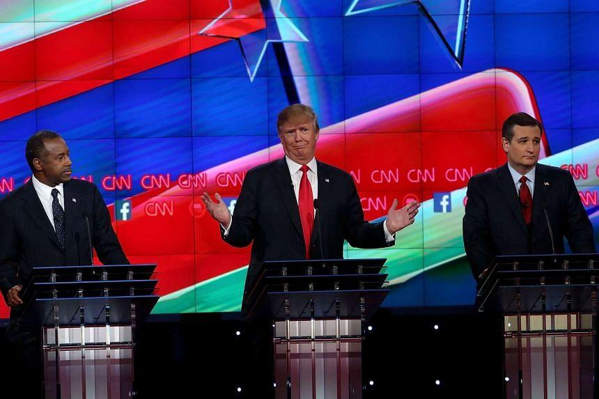 Republican presidential candidate Donald Trump (centre) speaking as Ben Carson (left) and US Senator Ted Cruz listen during the CNN Republican presidential debate on Dec 15, 2015.