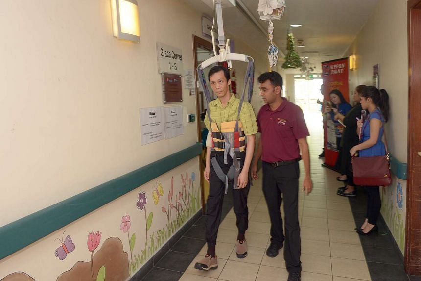 Rehab client Mr Chang Phan Yong, 41, moving around with the help of the ceiling patient hoist at The Salvation Army Peacehaven Nursing Home.