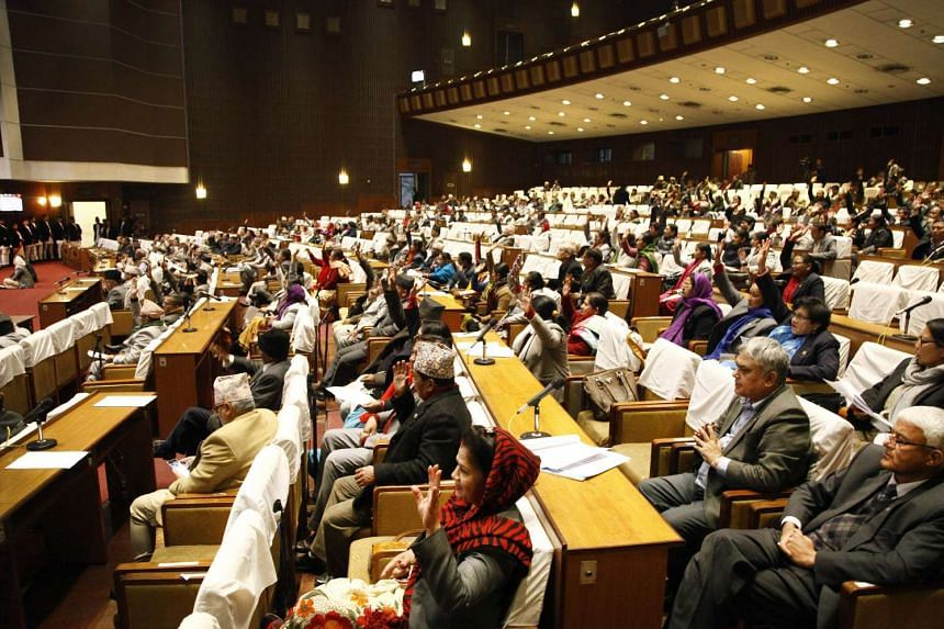Nepalese parliamentarians gesture while voting to pass a long-delayed bill in Kathmandu on Dec 16, 2015.