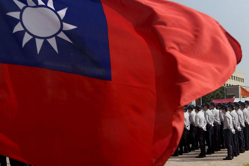 Members of the National Security Bureau take part in a drill next to a national flag at its headquarters in Taipei, Taiwan, Nov 13, 2015.