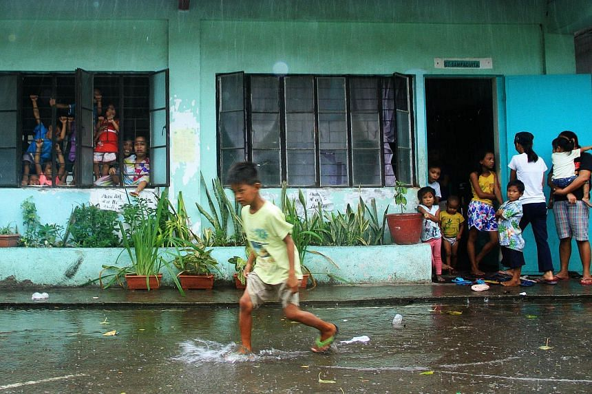 A young evacuee wades through flooded school grounds while others look on from a school building being used as an evacuation center in the city of Legaspi in Albay province, south of Manila on Dec 14, 2015.