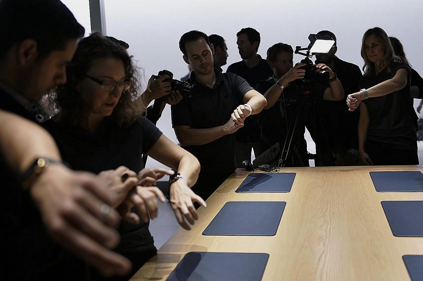 Attendees trying on the Apple Watch during an event. A report commissioned by the Singapore Exchange on top digital trends, released yesterday, noted that the growth of tech wearables, which include electronic technologies or computers incorporated i