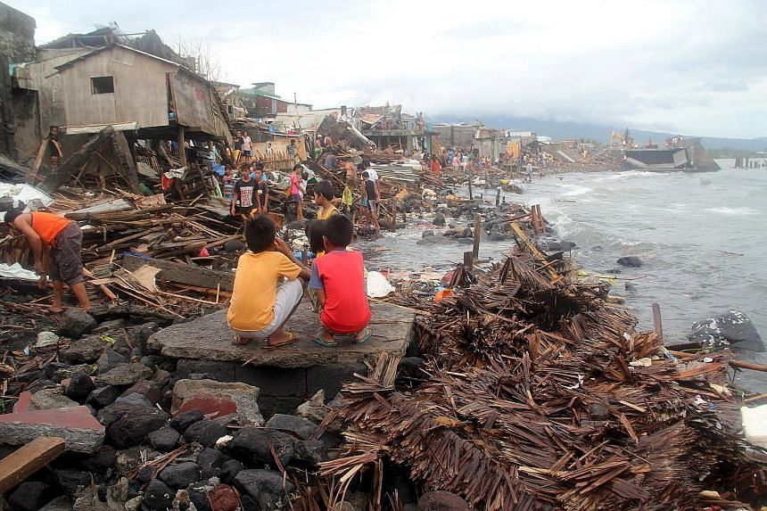 Villagers surveying the devastation in the coastal village of Pigcale after Typhoon Melor swept through Legazpi city, in the Philippines' Albay province, yesterday. Four people were killed and millions were left without power after the typhoon barrel