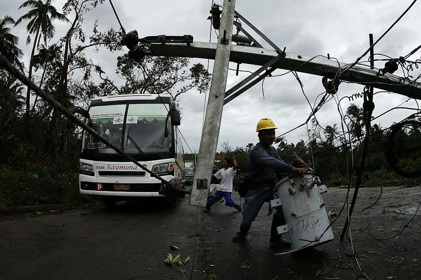 Above: Residents surveying the damage wrought by Typhoon Melor yesterday after it battered the town of Barcelona, in Sorsogon province in the central Philippines. Right: Workers clearing a fallen electric post in Castilla, Sorsogon province. Cold nor