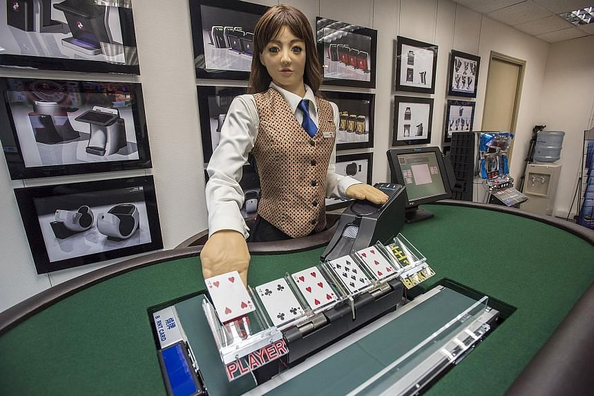 Min, a prototype human-like electronic croupier, dealing a card during a demonstration at the headquarters of Paradise Entertainment in Macau yesterday. Paradise, a Hong Kong-based gaming machine manufacturer and supplier, says the robot could cut la