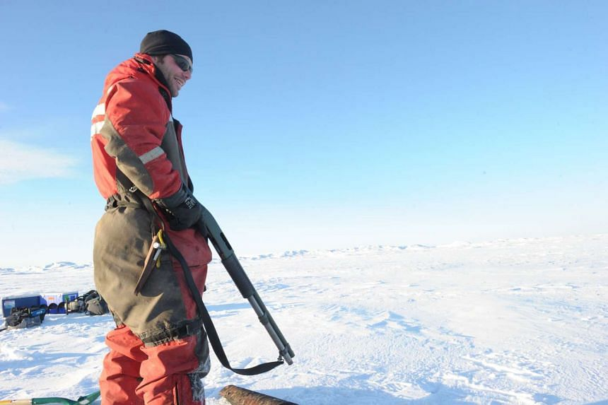 A Canadian Coast Guard member protects scientists from polar bears in the Canadian High Arctic.