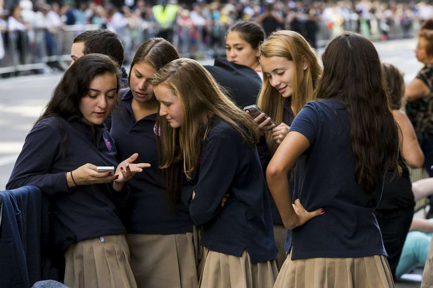 A group of schoolgirls check their mobile phones.