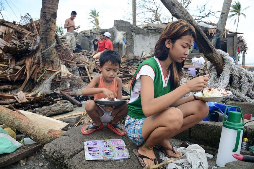 Residents eat outside of their damaged shanties after strong winds and heavy rains brought by typhoon Melor battered Barcelona town, Sorsogon province, central Philippines on Dec 15, 2015.