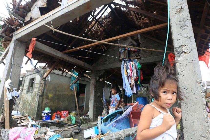 Residents are seen at their damaged houses after strong winds and heavy rains brought by typhoon Melor battered Barcelona town, Sorsogon province, central Philippines on Dec 15, 2015.