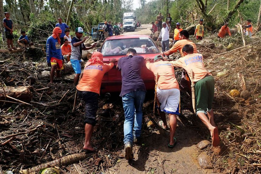 Filipino workers attempt to free a stuck vehicle in the typhoon-hit town of Matnog, Sorsogon province, southern Manila, Philippines, on Dec 15, 2015.