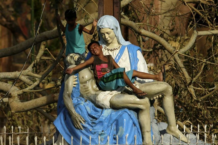 Filipino children play next to a Jesus and Mary statue in the typhoon-hit town of Bulan, Sorsogon province, southern Philippines, on Dec 15, 2015.