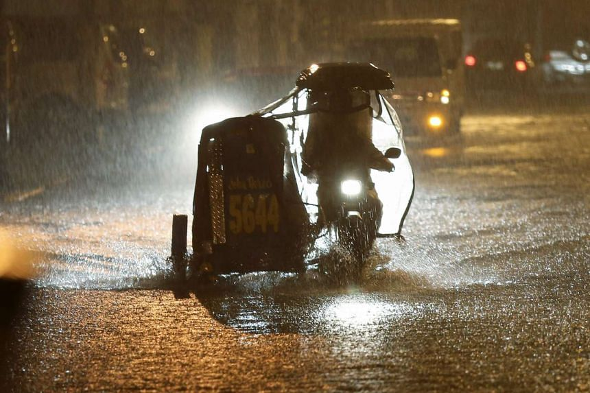 A vehicle drives down a flooded street as heavy rain pours in Makati city, south of Manila, Philippines, on Dec 15, 2015.