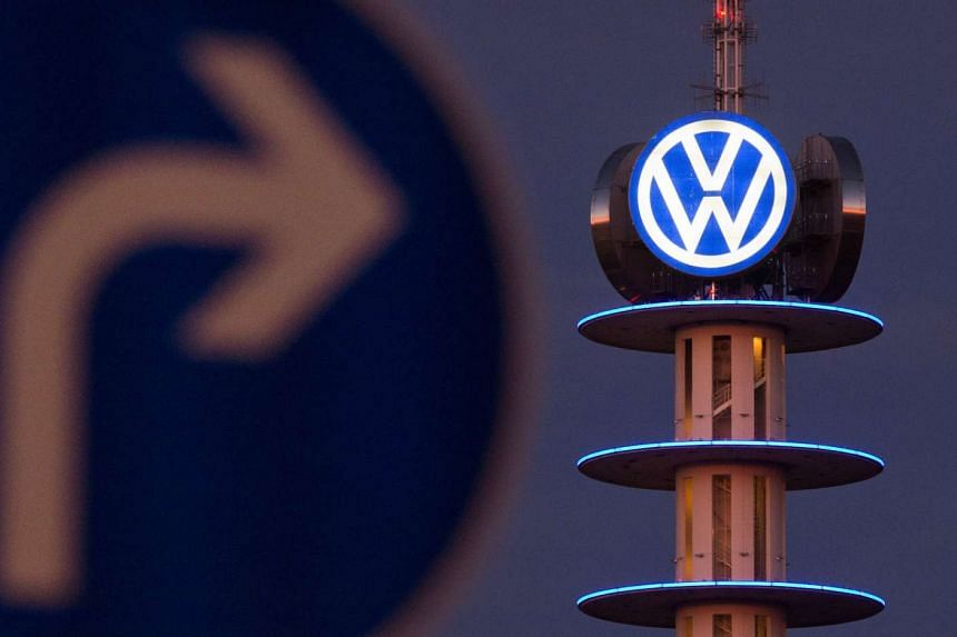 A street sign can be seen in front of the illuminated logo of German car maker Volkswagen on Dec10 in Hanover, central Germany.