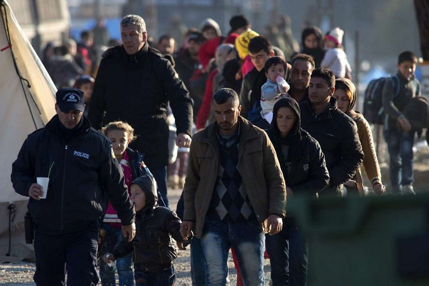 A Greek police officer leads a group of refugees towards the Greek-Macedonian border.