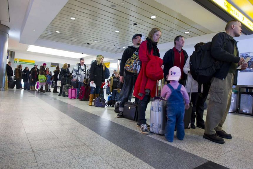 Travellers wait in line at the Central Terminal at LaGuardia Airport in the Queens borough of New York on Dec 28, 2010.