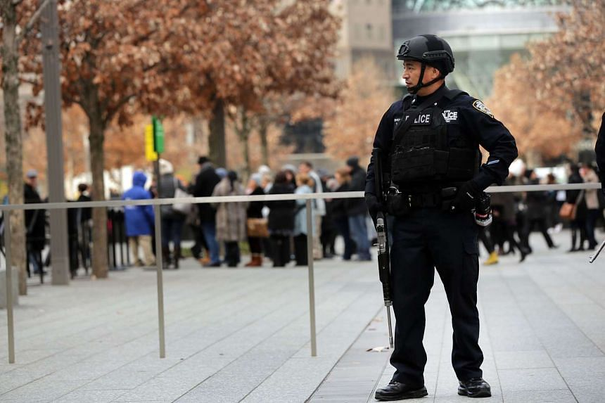 A New York City police officer stands guard near One World Trade Center in lower Manhattan on Nov 24, 2015.