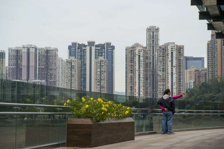 A couple posing for a selfie as residential buildings stand in the distance in Macau on Dec 6.