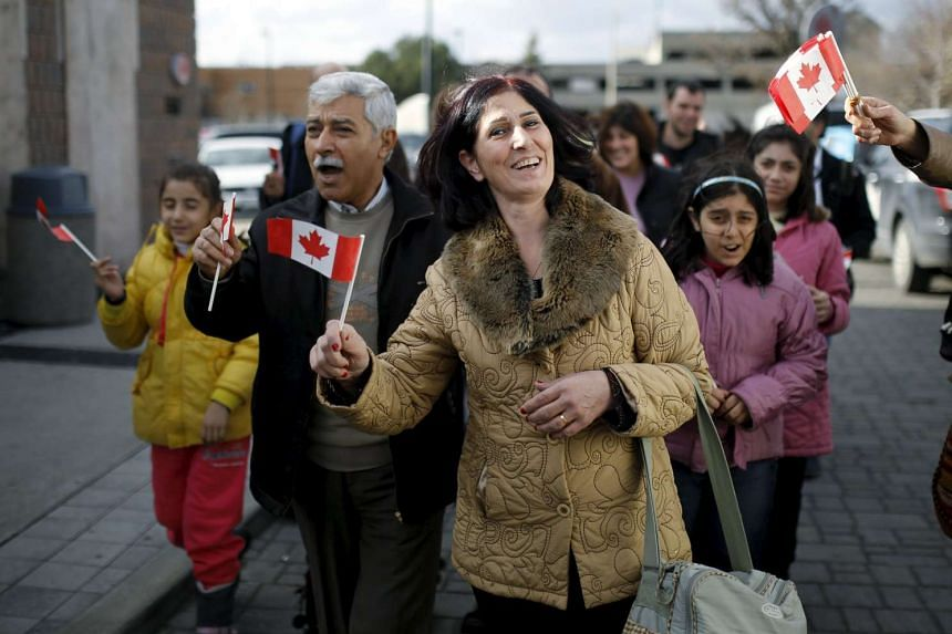 Syrian refugees Elo Manushian (centre) arrives with her husband Hagop (second left) at the Armenian Community Centre of Toronto.