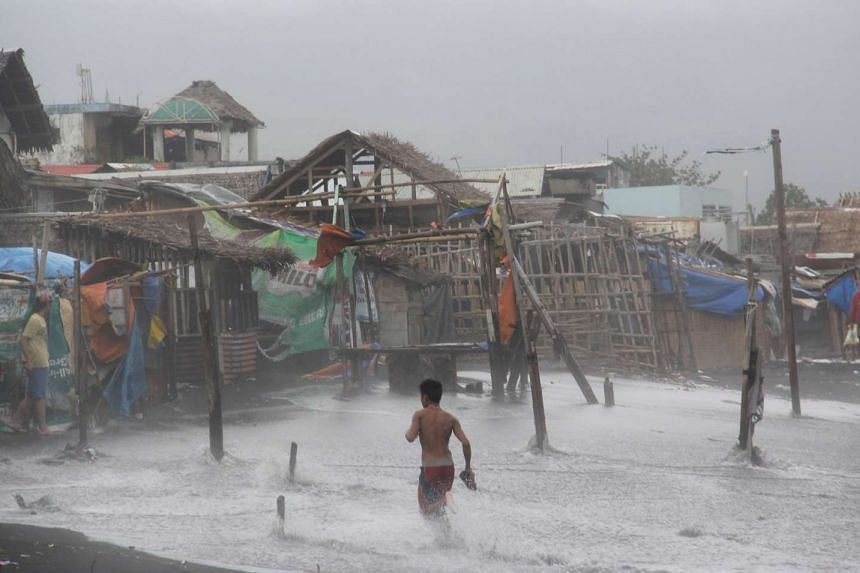 Residents in a coastal area are battered by strong winds and heavy rains brought by typhoon Melor.