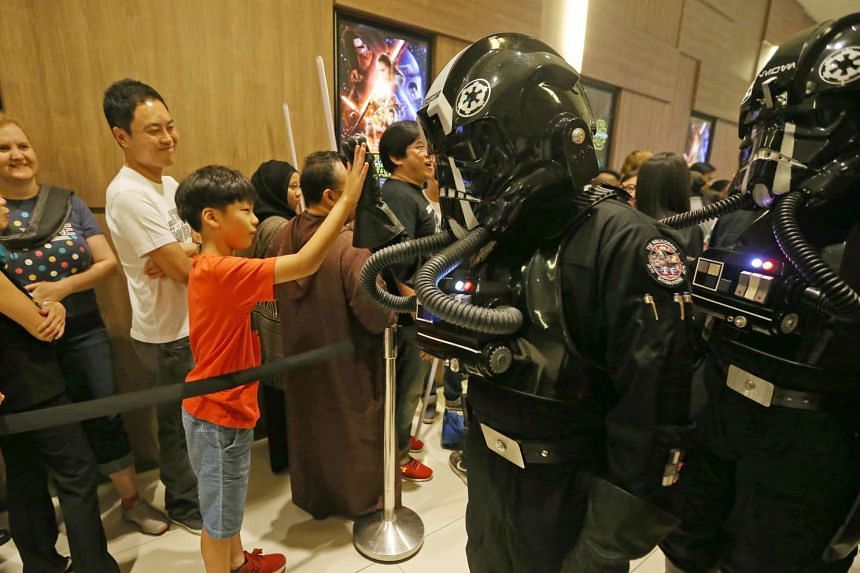It's a high five with a Star Wars character at the gala premiere of Star Wars: The Force Awakens on Dec 16, 2015.